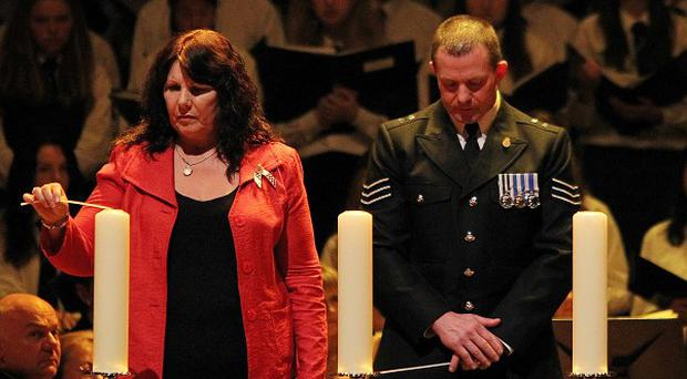 Kate Carroll (left) widow of PSNI Officer Stephen Carroll, lights a candle during the ceremony
