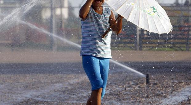 A girl plays in the sprinklers to beat the heat in Monterey Park, California (AP)