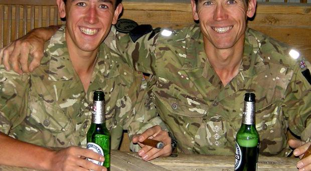 Captain Christopher Wilcock, 41, sharing a non-alcoholic beer with his son Marine James Hoyes, 22, at Camp Bastion, Afghanistan