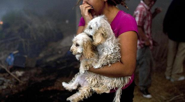A woman leaves the site of a fire on the outskirts of Tijuana, northern Mexico (AP)