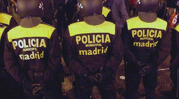 Police guard a bus depot during a nationwide general strike in Madrid