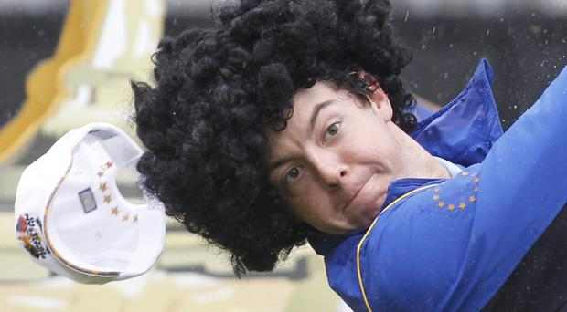 Europe's Rory McIlroy wearing a curly wig hits a tee shot during a practice round at the 2010 Ryder Cup golf tournament at the Celtic Manor golf course in Newport, Wales, Wednesday, Sept. 29, 2010