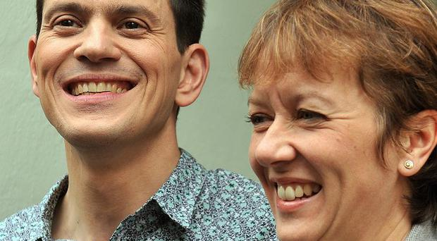 David Miliband and his wife Louise stand on the steps of their north London home