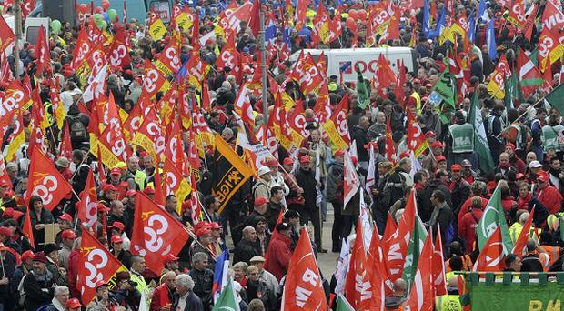 Demonstrators march down a main boulevard in Brussels to protest against spending cuts