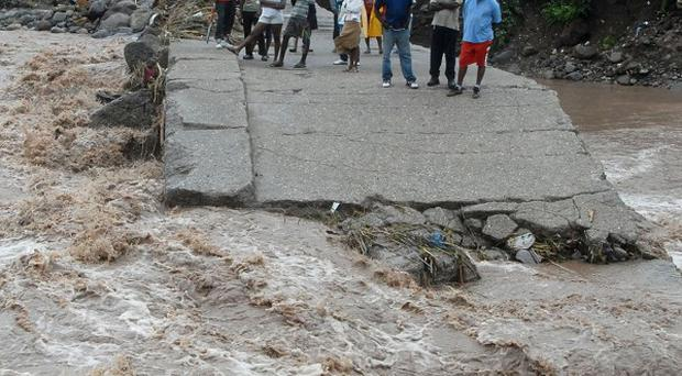 Residents watch floodwater as they stand on a destroyed bridge in Jamaica (AP)