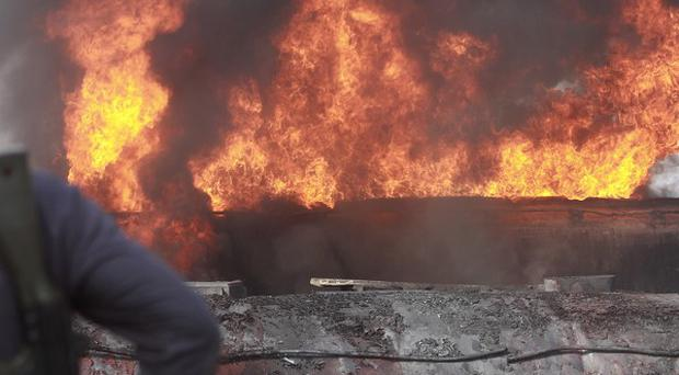A Pakistani policeman keeps watch on oil trucks set ablaze in Shikarpur (AP)