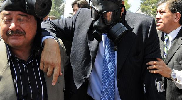 Wearing a gas mask, Ecuador's President Rafael Correa, centre, is helped to escape from tear gas during a protest (AP)