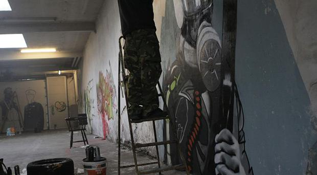 A squatter paints a mural in a former fire department building in Amsterdam