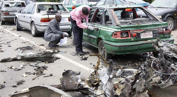 Officials inspect the remains of a car after a car bomb exploded in Abuja, Nigeria (AP)