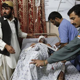 A wounded Aghan policeman is brought to a hospital in Kandahar after three explosions rocked the city (AP)