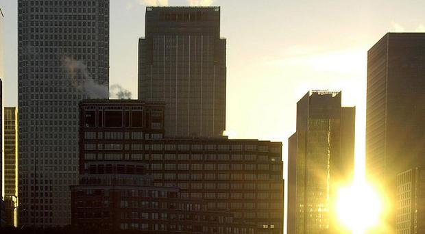 The sun rises over Canary Wharf after figures were published showing City workers' cash bonuses would top £7 billion this year