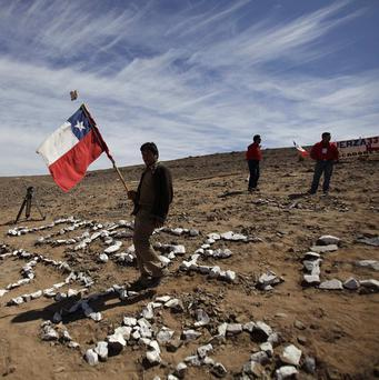 A man carries a Chilean flag during a small ceremony marking 60 days since 33 miners became trapped in Chile (AP)