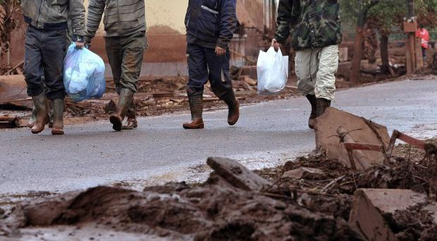 People carry salvaged belongings from their homes flooded by toxic mud in the Kolontar, Hungary