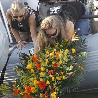 Family members lay a wreath near the site where David Hartley was shot dead last week on Falcon Lake in Zapata, Texas (AP)