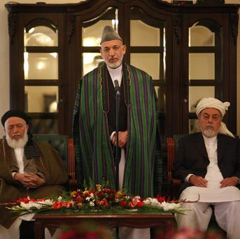 Afghan President Hamid Karzai, centre, speaks during the inaugural session of Afghanistan's new peace council