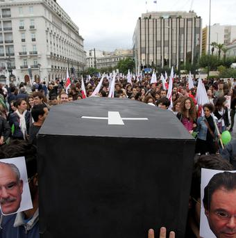 Protesters covering their faces with photos of Greek politicians carry a symbolic coffin during a protest in Athens (AP)