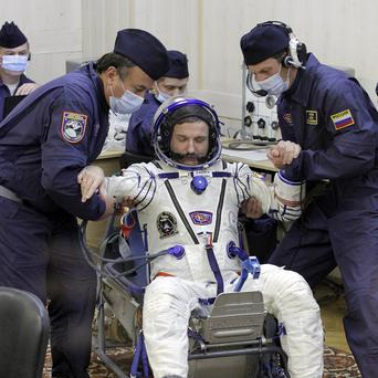 Russian Space Agency experts help cosmonaut Alexander Kaleri to stand up after inspecting his space suit (AP)