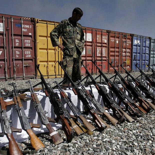 An Afghan policeman looks at weapons confiscated from private security companies in Kabul, Afghanistan (AP)