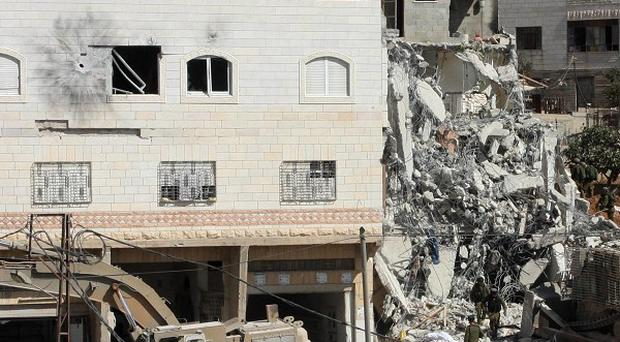 Israeli soldiers demolish a house after troops killed two senior Hamas militants in Hebron (AP)