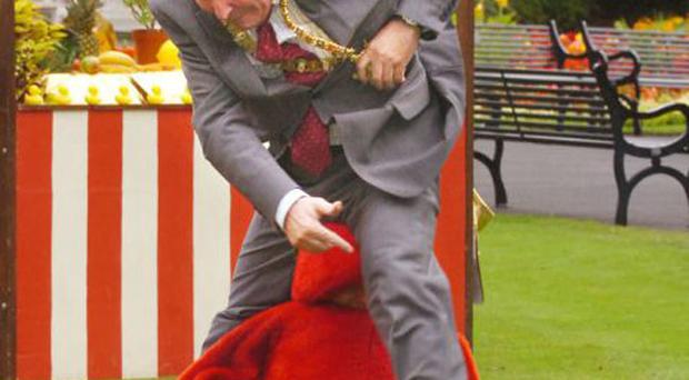 Jim Rogers attempts to jump over council worker Lorraine Mallon (dressed in a tomato costume)