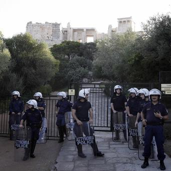 Riot police stand guard at the entrance of ancient Acropolis site in Athens (AP)