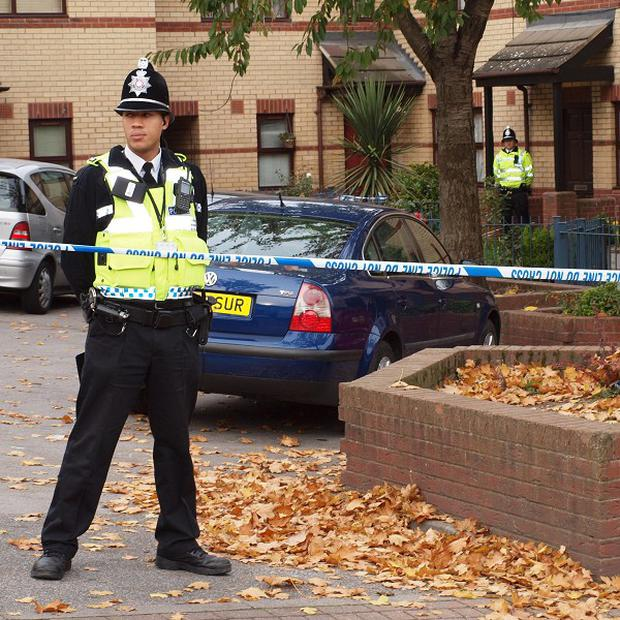A policeman guards the scene in Cloudsdale Avenue, Bradford, where a woman was found on fire behind a house