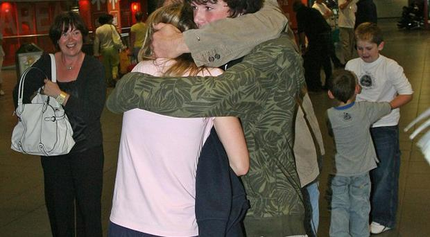 One of the trainees rescued from life rafts after the Asgard II went down off the coast of France is hugged by her family. A report says the boat hit something underwater