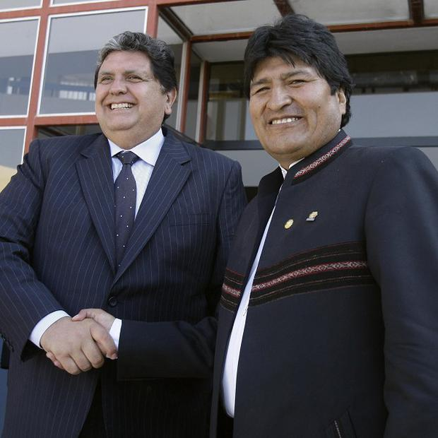 Peru's President Alan Garcia, left, and Bolivia's President Evo Morales shake hands after a meeting in the port of Ilo, southern Peru