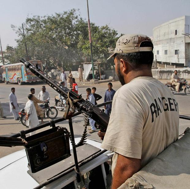 A soldier observes pedestrians in Karachi after gunmen opened fire in a commercial market (AP)