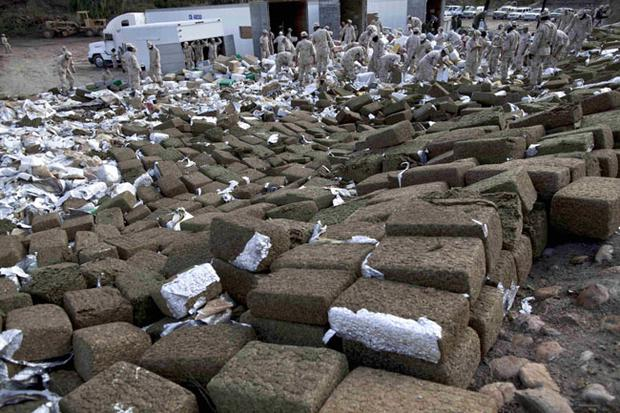 Soldiers work on packages of seized marijuana prior to incinerating them in Tijuana, Mexico, Wednesday, Oct. 20, 2010