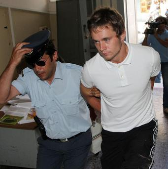 Luke Walker is escorted by police as he leaves the court in the city of Iraklio on the Greek island of Crete (AP)