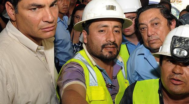 Miners show Ecuador's President Rafael Correa, left, the work being done to rescue a trapped miner at the Casa Negra mine in Portovelo, Ecuador (AP)
