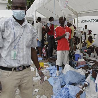 People are treated in the car park of the St Nicholas hospital in Saint Marc, Haiti, after an outbreak of suspected cholera which has killed 135