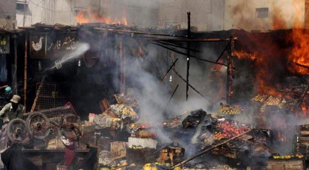 Angry demonstrators in Pakistan set fire to roadside shops in a street protest against the recent killings in Karachi (AP)