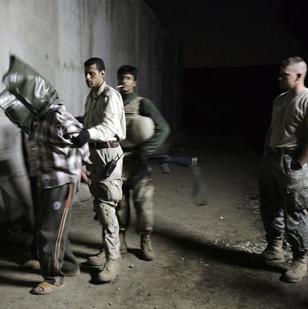 A US Army soldier, right, looks on as an Iraqi Army soldier escorting two hooded men detained in a raid by Iraqi troops in Mosul. (AP)