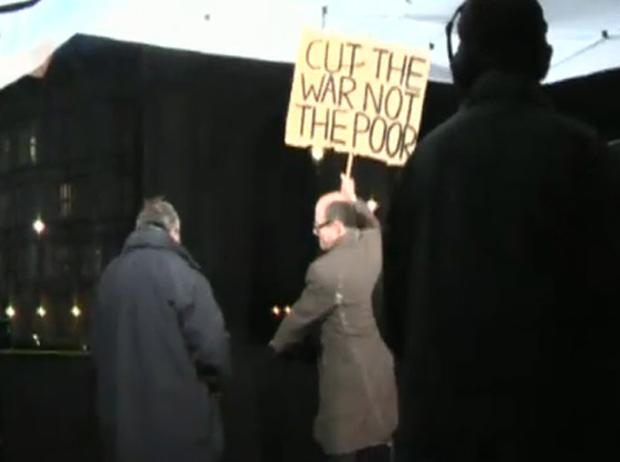 In the footage Mr Robinson is shown trying to pull apart the sign - which read 'Cut the war not the poor' - before stamping on it, while a protester shouts: 'You should be ashamed of yourself, mate.'