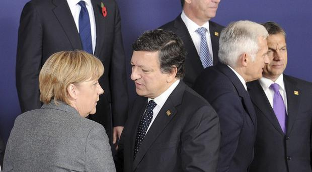 European Commission President Jose Manuel Barroso, shares a word with German Chancellor Angela Merkel as David Cameron watches on (AP)