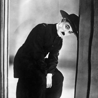 A Charlie Chaplin film shows a woman using what appears to be a mobile phone