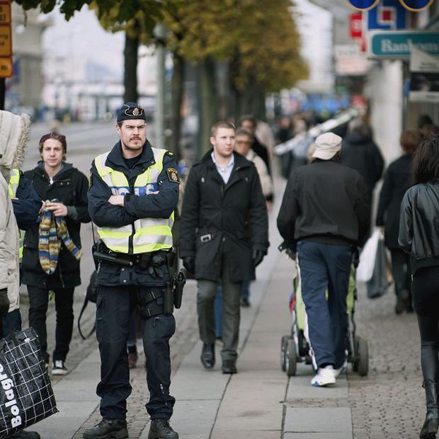Policemen patrol central Gothenburg, Sweden, following a reported bomb plot (AP)
