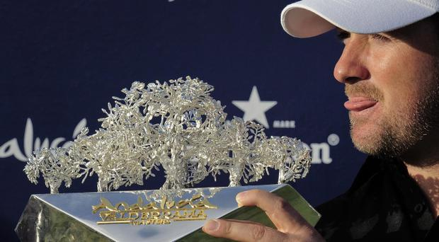 Graeme McDowell holds the trophy after winning the Volvo Masters golf tournament in Sotogrande, Spain