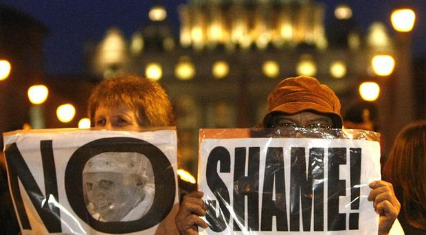 Demonstrators hold placards during a protest near St. Peter's Square, Rome, on Sunday
