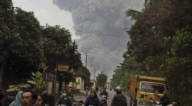 Residents in Central Java, Indonesia, flee on their motorcycles as Mount Merapi erupts behind them