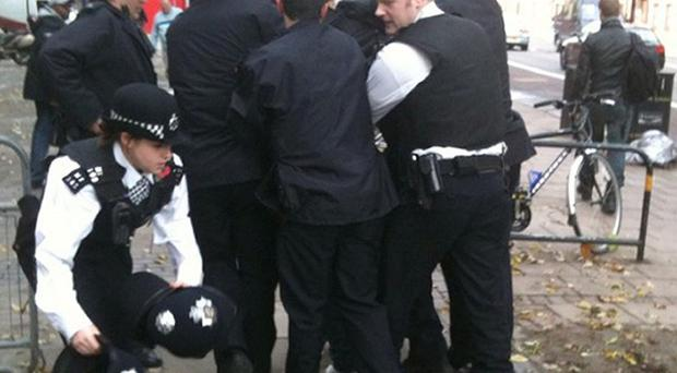 Police restrain a man outside Highbury Magistrates' Court after he allegedly attacked Shameless star Elliott Tittensor