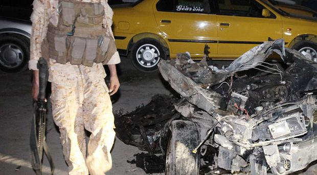A soldier next to wreckage from a car bomb in the Shiite neighbourhood of Sadr City in Baghdad, Iraq (AP)