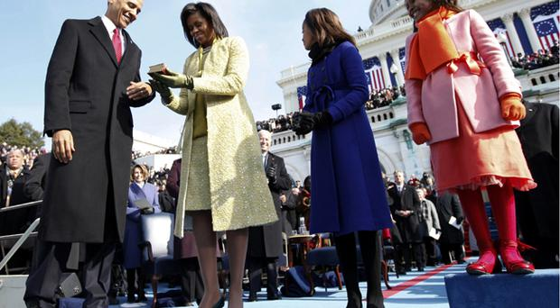 <b>So much can change in two years- flashback to Obama's inauguration </b>........Barack Obama and wife, Michelle, examine the Bible used for his swearing-in ceremony as the 44th president of the United States as their daughters Malia and Sasha (with the aid of a box) look on