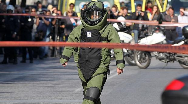 A police explosive expert prepares a controlled blast in Athens (AP)
