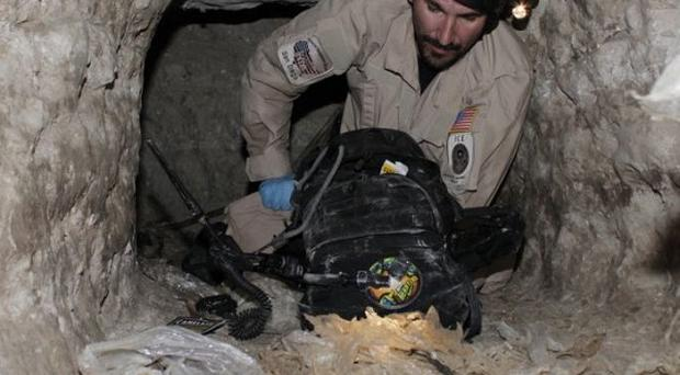 A US federal agent crawls through a tunnel found in a warehouse along the border between the United States and Mexico