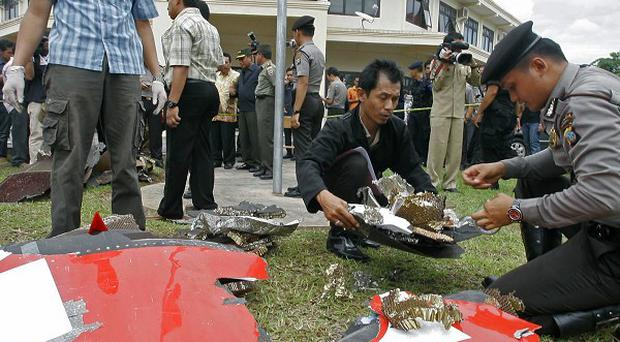 Indonesian police officers inspect parts of the Qantas plane that were found on the island of Batam near Singapore (AP)