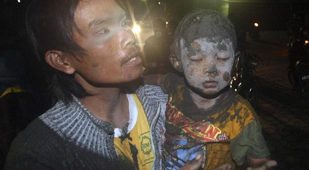 A man and a boy flee following another eruption Mount Merapi in Indonesia (AP)