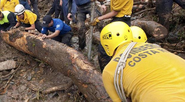 Rescuers remove a tree trunk while searching for bodies after a landslide in Costa Rica (AP)